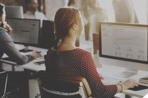 um homem e uma mulher trabalhando no computador em uma agência de marketing