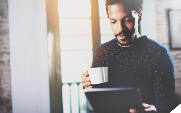 Pequeno empresário usando o tablet e tomando café